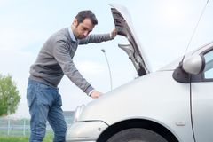 Man and car engine breakdown problem. Stressed man checking engine after vehicle breakdown Royalty Free Stock Photo
