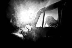 Man in car full of smoke Royalty Free Stock Photo