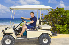 Man on car for golf at seeshore. Royalty Free Stock Photo