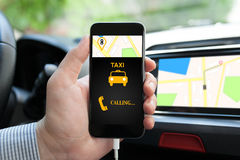 Man in car holding phone with app taxi on screen Royalty Free Stock Photos