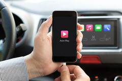 Man in car holding phone with Auto Play multimedia system Royalty Free Stock Image