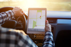 Man in car and holding tablet with map gps navigation. Man sitting in car and holding tablet with map gps navigation, toned at sunset Royalty Free Stock Photos