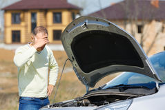 Man and car. Irritation man in a broken car open hood Royalty Free Stock Images