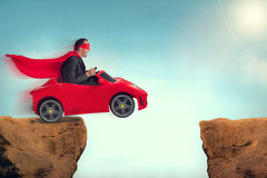Man in a car jumping a ravine. Man in a red car jumping a ravine Royalty Free Stock Images