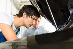 Man and car mechanic looking beneath a hood Stock Photography