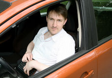Man in car with netbook Stock Image