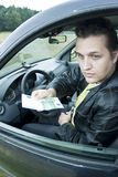 Man in car offering money stock image