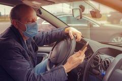 A man in a car with a phone in his hand and a protective mask against the spread of Coronavirus