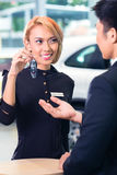 Man at car rental receiving key Royalty Free Stock Photography