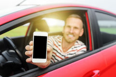 Man in car showing smart phone. Stock Photography