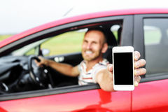 Man in car showing smart phone. Royalty Free Stock Photography