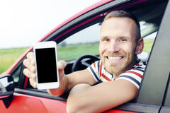 Man in car showing smart phone. Man in car showing smart phone display smiling happy. Focus on model. Toned photo royalty free stock photo