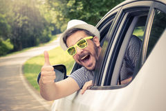 Man in car showing thumbs up. Young man wearing hat and sunglasses showing thumbs up from driver's seat through opened window. Vacation and travel stock photography