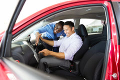 Man car showroom. Happy middle aged men checking car features in showroom Royalty Free Stock Images