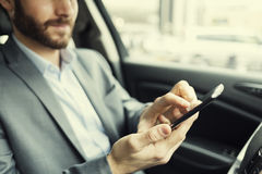 Man in car typing text message on mobile phone. Businessman using his smartphone in a car Stock Image