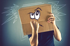 Man with cardboard box on his head and doodle drawing of angry f Royalty Free Stock Image