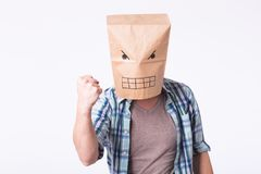 Man with cardboard box on his head and drawing of angry emoticon face. Angry man starting a fight. Man with cardboard box on his head and drawing of angry Royalty Free Stock Photography