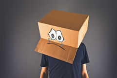 Man with cardboard box on his head and sad face expression Stock Image
