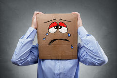 Man with cardboard box on his head showing sad expression Royalty Free Stock Photos