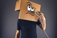 Man with cardboard box on his head using tin can telephone. For conversation. Angry face expression Stock Image