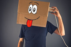 Man with cardboard box on his head using tin can telephone Stock Images