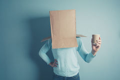 Man with cardboard box over head and a cup Royalty Free Stock Image