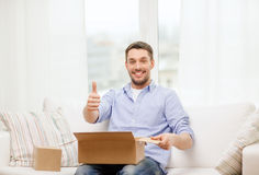 Man with cardboard boxes at home showing thumbs up Royalty Free Stock Image