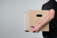 Man with a cardboard in his hands, isolated on grey Stock Image