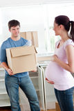 Man with cardboard looking at his pregnant wife Royalty Free Stock Photo