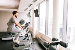 Man cardio training on a bicycle. In a gym royalty free stock images