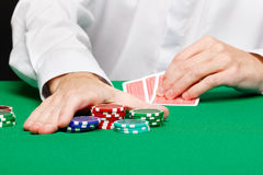 Man with cards. Man's hand with cards and chips on a gambling table Stock Image