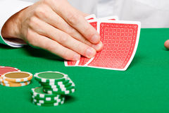 Man with cards on a gambling table. Casino. Man's hand with cards and chips on a gambling table stock image