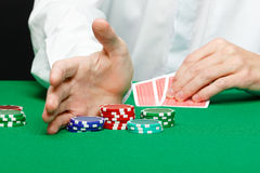 Man with cards on a gambling table. Casino. Man's hand with cards and chips on a gambling table Stock Photo