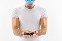 Man carefully keeping some soil. Healthy beginning. Male person in mask is holding handful of ground with little sprout Stock Photography