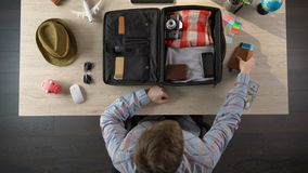 Man carefully packing suitcase for travel, taking money and documents, top view. Stock footage stock video footage