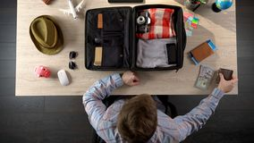 Man carefully packing suitcase for travel, taking money and documents, top view. Stock photo Stock Photos