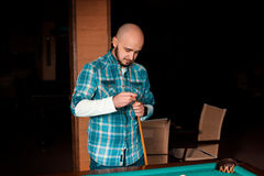 Man carefully prepares his cue with chalk to hitting Stock Image