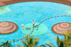 Man carefully walking on stepping stones through water pool in Durban, South Africa Stock Photo