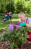 Man cares for flowers while his wife is resting Royalty Free Stock Photos