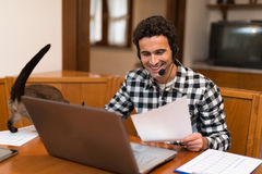 Man caressing his cat while working at home Royalty Free Stock Image