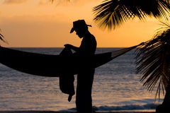 Man in caribbean sunset. Man with cowboy hat standing beside a hammock (caribbean sunset Royalty Free Stock Photos