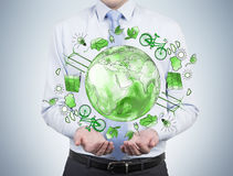 Man caring about clean environment, eco energy, protection. Man as if holding a sphere with a green picture of eco energy icons arranged in circle, earth in the Stock Photography