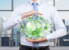 Man caring about clean environment, eco energy, protection. Man as if holding a sphere with a green picture of eco energy icons arranged in circle, earth in the Royalty Free Stock Photos