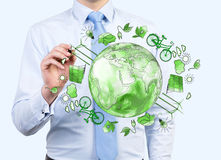 Man caring about clean environment, eco energy, protection. Man pointing at the green picture of eco energy icons arranged in circle, earth in the centre Stock Image