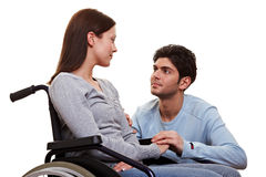 Man caring for girlfriend. Young man caring for his disabled girlfriend in wheelchair Royalty Free Stock Photos