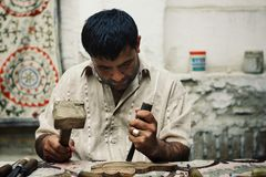 Man caring traditional wooden artifact in the historical walled city of the silk road stock photo