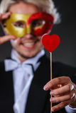 Man in carnival mask with heart stick love symbol Stock Photo