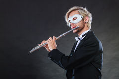 Man in carnival mask playing flute Stock Photos