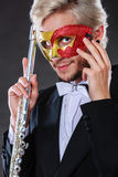 Man in carnival mask playing flute Stock Photography