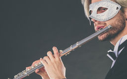 Man in carnival mask playing flute Royalty Free Stock Photos